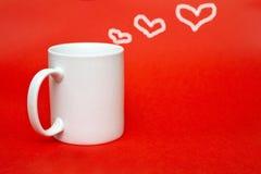 Άσπρη κούπα στο κόκκινο υπόβαθρο με την καρδιά Διάστημα αντιγράφων για το γράψιμο Γυαλί που απομονώνεται άσπρο Έννοια ημέρας του  Στοκ φωτογραφίες με δικαίωμα ελεύθερης χρήσης