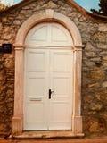 Άσπρη ξύλινη πόρτα στην παλαιά οδό Στοκ Φωτογραφία