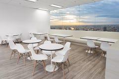 Άσπρη ξύλινη καρέκλα στη τραπεζαρία του σύγχρονου γραφείου με τα παράθυρα στοκ εικόνες
