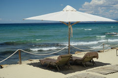 Άσπρη ομπρέλα με τα κενές κρεβάτια και τις πετσέτες παραλιών στην Ελλάδα Στοκ Εικόνες