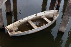 Άσπρη παλαιά leaky βάρκα μισή στο νερό στον ποταμό στοκ εικόνες
