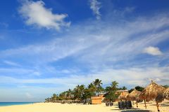 Άσπρη παραλία άμμου και τυρκουάζ ωκεανός νερού στους πράσινους φοίνικες και το υπόβαθρο μπλε ουρανού Στοκ εικόνα με δικαίωμα ελεύθερης χρήσης