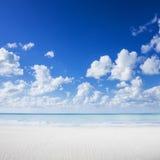 Άσπρη παραλία άμμου, τροπικοί ωκεανός και μπλε ουρανός Στοκ Εικόνες