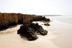 Άσπρη παραλία και μαύροι βράχοι πετρών Στοκ φωτογραφία με δικαίωμα ελεύθερης χρήσης