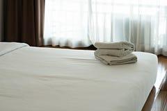 Άσπρη πετσέτα καθορισμένη και κρεβάτι στο σύγχρονο ξενοδοχείο Στοκ Φωτογραφία