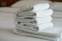 Άσπρη πετσέτα καθορισμένη και κρεβάτι στο σύγχρονο ξενοδοχείο Στοκ φωτογραφίες με δικαίωμα ελεύθερης χρήσης