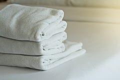 Άσπρη πετσέτα καθορισμένη και κρεβάτι στο σύγχρονο ξενοδοχείο Στοκ εικόνα με δικαίωμα ελεύθερης χρήσης