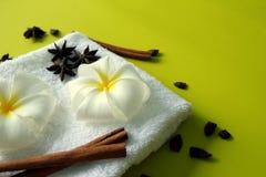 Άσπρη πετσέτα με τα λουλούδια του plumeria με τα αστέρια των ραβδιών γλυκάνισου και κανέλας στο κίτρινο υπόβαθρο Στοκ εικόνες με δικαίωμα ελεύθερης χρήσης