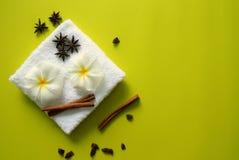 Άσπρη πετσέτα με τα λουλούδια του plumeria με τα αστέρια των ραβδιών γλυκάνισου και κανέλας στο κίτρινο υπόβαθρο Στοκ Εικόνες