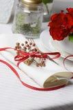 Άσπρη πετσέτα που διακοσμείται με τις κόκκινες εγκαταστάσεις Χριστουγέννων κορδελλών, επιτραπέζιο SE Στοκ Εικόνα