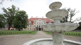 Άσπρη πηγή κοντά στο κίτρινο κάστρο στη Λετονία απόθεμα βίντεο