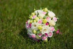 Άσπρη πράσινη, ρόδινη και κίτρινη και ρόδινη γαμήλια ανθοδέσμη με τα τριαντάφυλλα στη χλόη Ζωηρόχρωμη εικόνα του όμορφου μπουκέτο Στοκ φωτογραφία με δικαίωμα ελεύθερης χρήσης