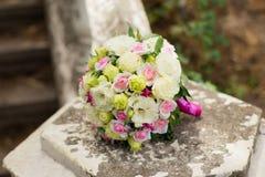 Άσπρη πράσινη, ρόδινη και κίτρινη και ρόδινη γαμήλια ανθοδέσμη με τα τριαντάφυλλα στην πέτρα Ζωηρόχρωμη εικόνα του όμορφου μπουκέ Στοκ φωτογραφία με δικαίωμα ελεύθερης χρήσης