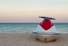Άσπρη προβολή ύδατος μηχανικών δίκυκλων με το κόκκινο στην ακτή ακτή, παραλία, μπλε ουρανός Στοκ Εικόνες
