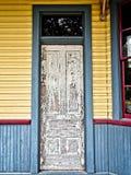Άσπρη πόρτα αποφλοίωσης με τον μπλε & κίτρινο τοίχο Στοκ εικόνες με δικαίωμα ελεύθερης χρήσης