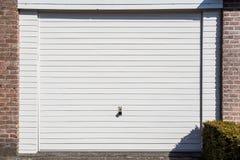 Άσπρη πόρτα γκαράζ ενός αποσυνδεμένου σπιτιού στοκ εικόνες