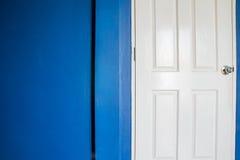 Άσπρη πόρτα και μπλε ναυτικός τοίχος Στοκ Φωτογραφίες