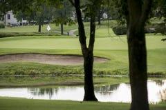 Άσπρη σημαία πέρα από το πολύβλαστο γκολφ πράσινο μέσω των δέντρων Στοκ φωτογραφία με δικαίωμα ελεύθερης χρήσης