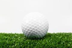 Άσπρη σφαίρα γκολφ στην πράσινη χλόη στο πίσω μέρος του άσπρου πατώματος Στοκ Φωτογραφίες