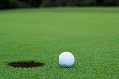 Άσπρη σφαίρα γκολφ στην τοποθέτηση πράσινη Στοκ Φωτογραφία