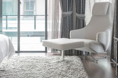 Άσπρη σύγχρονη καρέκλα στον τάπητα στη σύγχρονη κρεβατοκάμαρα Στοκ φωτογραφίες με δικαίωμα ελεύθερης χρήσης