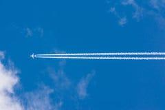 Άσπρη σύννεφων ηλιόλουστη ημέρα ιχνών αεροπλάνων φλογών ήλιων μπλε ουρανού χνουδωτή στοκ εικόνες