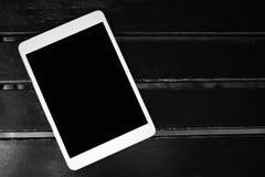 Άσπρη ταμπλέτα οθονών επαφής με τη μαύρη κενή διαστημική οθόνη αντιγράφων για τη διαφήμιση ή κοινωνικό κείμενο μέσων στο μαύρο ξύ στοκ εικόνα