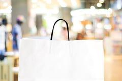 Άσπρη τσάντα αγορών πέρα από το θολωμένο υπόβαθρο καταστημάτων Στοκ εικόνες με δικαίωμα ελεύθερης χρήσης