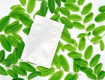 Άσπρη τσάντα κρέμας στην κενή συσκευασία ετικετών για τη χλεύη επάνω σε ένα πράσινο υπόβαθρο φύλλων Η έννοια των φυσικών προϊόντω Στοκ εικόνες με δικαίωμα ελεύθερης χρήσης