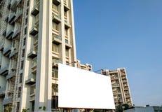 άσπρη χλεύη ψαλιδίσματος επάνω για τη διαφήμιση με κάποια διακόσμηση κάτω από το τεράστιο ψηλό κτίριο στοκ φωτογραφία