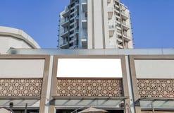 άσπρη χλεύη ψαλιδίσματος επάνω για τη διαφήμιση με κάποια διακόσμηση κάτω από το τεράστιο ψηλό κτίριο στοκ φωτογραφία με δικαίωμα ελεύθερης χρήσης