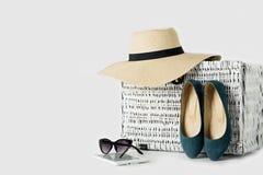 Άσπρη ψάθινη βαλίτσα, καπέλο των γυναικών, γυαλιά ηλίου, μπλε παπούτσια και ε Στοκ Φωτογραφία