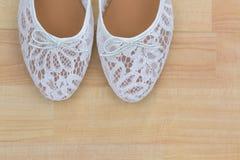 Άσπρη floral επίπεδη ολίσθηση μπαλέτου δαντελλών στα παπούτσια στο ξύλινο υπόβαθρο Στοκ Εικόνες