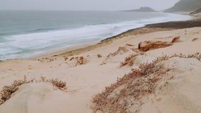 Άσπροι αμμόλοφοι άμμου και ηφαιστειακοί βράχοι, ωκεάνια κύματα που καταβρέχουν αργά ενάντια στην παραλία Calhau, ακρωτήριο νησιών φιλμ μικρού μήκους