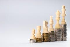 Άσπροι αριθμοί σκακιού που στέκονται στα νομίσματα που σημαίνουν την αύξηση δύναμης και σταδιοδρομίας Στοκ Φωτογραφίες