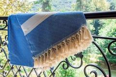 Άσπροι και μπλε τουρκικοί ένας peshtemal/μια πετσέτα στα κιγκλιδώματα ενός επεξεργασμένου σιδήρου με τη μουτζουρωμένη φύση στο υπ Στοκ Φωτογραφίες