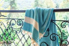 Άσπροι και τυρκουάζ τουρκικοί ένας peshtemal/μια πετσέτα στα κιγκλιδώματα ενός επεξεργασμένου σιδήρου με τη μουτζουρωμένη φύση στ Στοκ Εικόνες