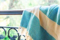 Άσπροι και τυρκουάζ τουρκικοί ένας peshtemal/μια πετσέτα στα κιγκλιδώματα ενός επεξεργασμένου σιδήρου με τη μουτζουρωμένη φύση στ Στοκ Φωτογραφία