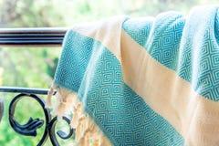 Άσπροι και τυρκουάζ τουρκικοί ένας peshtemal/μια πετσέτα στα κιγκλιδώματα ενός επεξεργασμένου σιδήρου με τη μουτζουρωμένη φύση στ Στοκ Εικόνα
