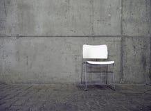 Άσπροι καρέκλα και συμπαγής τοίχος Στοκ Φωτογραφίες