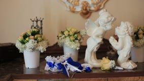 Άσπροι κεραμικοί άγγελοι συνεδρίασης που φιλούν στο υπόβαθρο λουλουδιών φιλμ μικρού μήκους