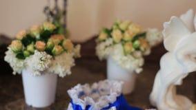 Άσπροι κεραμικοί άγγελοι συνεδρίασης που φιλούν στο υπόβαθρο λουλουδιών απόθεμα βίντεο