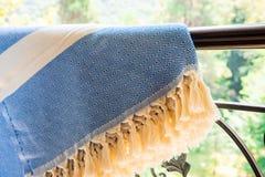 Άσπροι μπεζ και μπλε τουρκικοί ένας peshtemal/μια πετσέτα στα κιγκλιδώματα ενός επεξεργασμένου σιδήρου με τη μουτζουρωμένη φύση σ Στοκ Φωτογραφίες