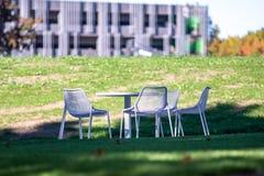 Άσπροι πίνακας και καρέκλες κήπων σε ένα patio patio έξω από ένα κτίριο γραφείων στοκ εικόνες