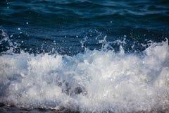 Άσπροι παφλασμοί του νερού σε ένα μπλε κύμα θάλασσας στοκ εικόνες