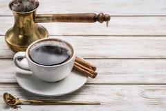 Άσπροι σωλήνες φλιτζανιών του καφέ και κανέλας, κουτάλι με τον επίγειο καφέ, turka δοχείων καφέ στον άσπρο ξύλινο πίνακα διάστημα Στοκ Φωτογραφίες