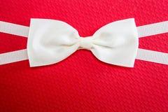 Άσπρος δεσμός τόξων στο κόκκινο υπόβαθρο κιβωτίων δώρων Στοκ Εικόνα