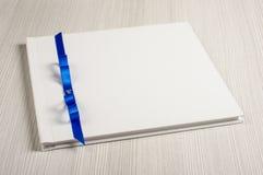 Άσπρος διακοσμημένος γάμος guestbook στο φωτεινό πίνακα Στοκ Εικόνα