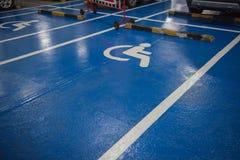 Άσπρος και μπλε χώρος στάθμευσης αυτοκινήτων συμβόλων αναπηρίας των ατόμων με ειδικές ανάγκες στο πάτωμα Στοκ εικόνες με δικαίωμα ελεύθερης χρήσης