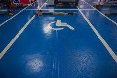 Άσπρος και μπλε χώρος στάθμευσης αυτοκινήτων συμβόλων αναπηρίας των ατόμων με ειδικές ανάγκες στο πάτωμα Στοκ Φωτογραφία